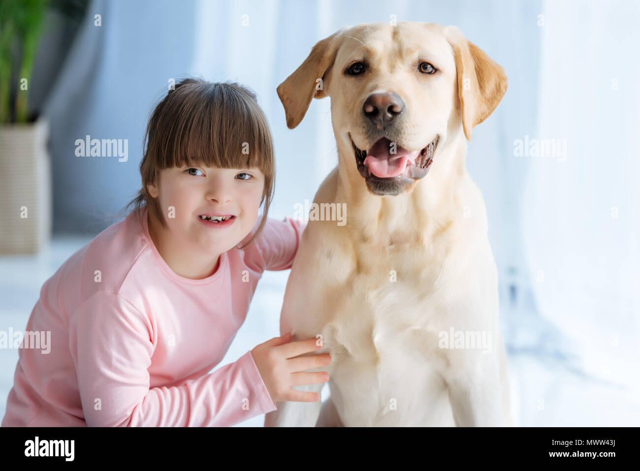 Happy child girl with down syndrome cherishing Labrador retriever - Stock Image