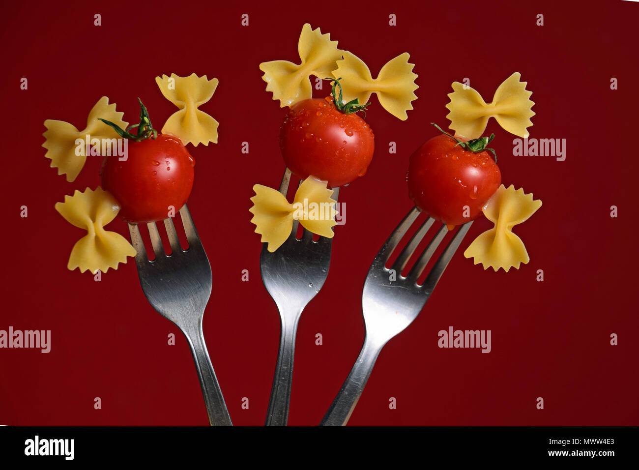 cherry tomatoes and bow tie past on forks on a red background - Stock Image