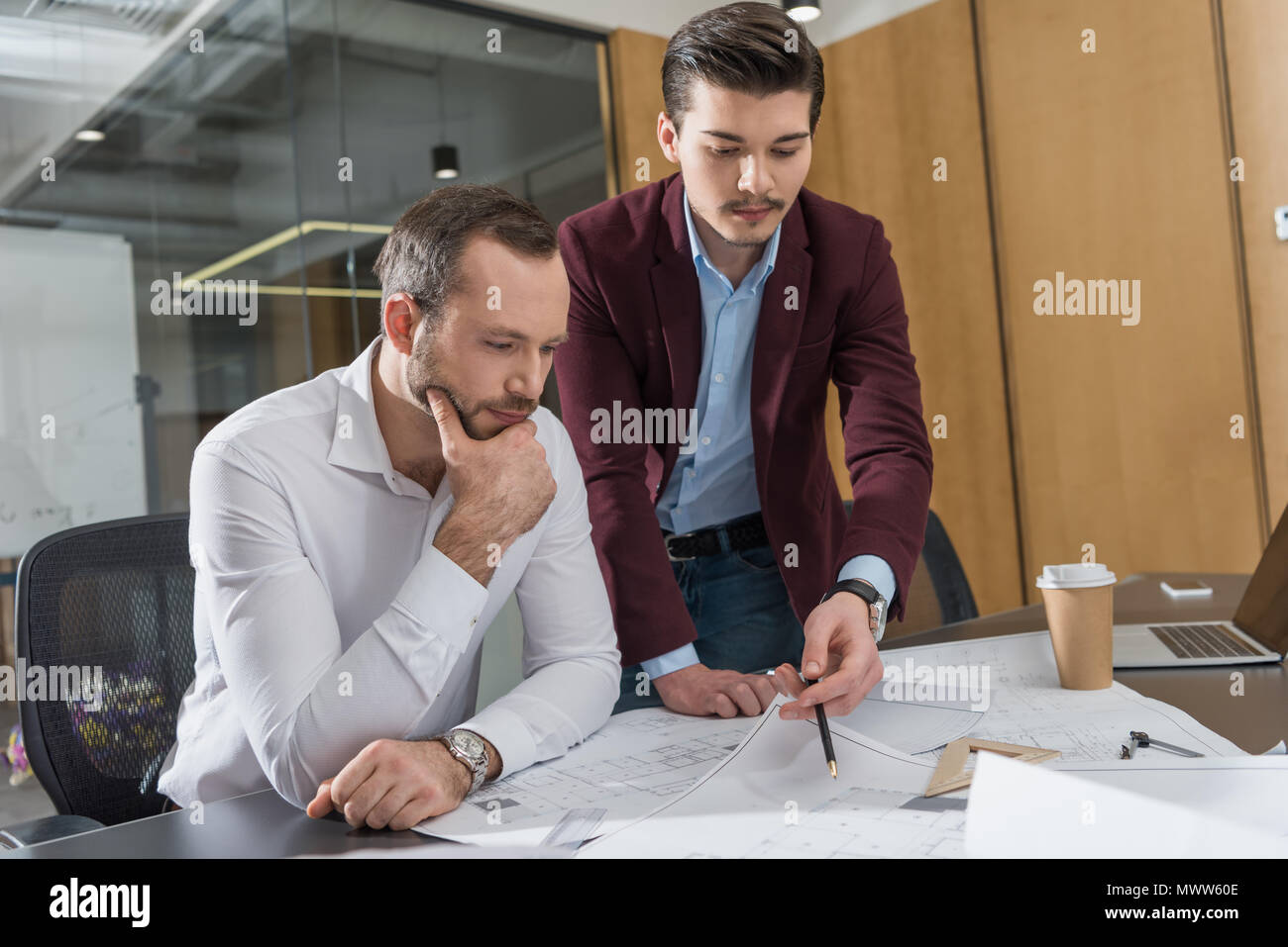 thoughtful architects brainstorming over building plans at office Stock Photo