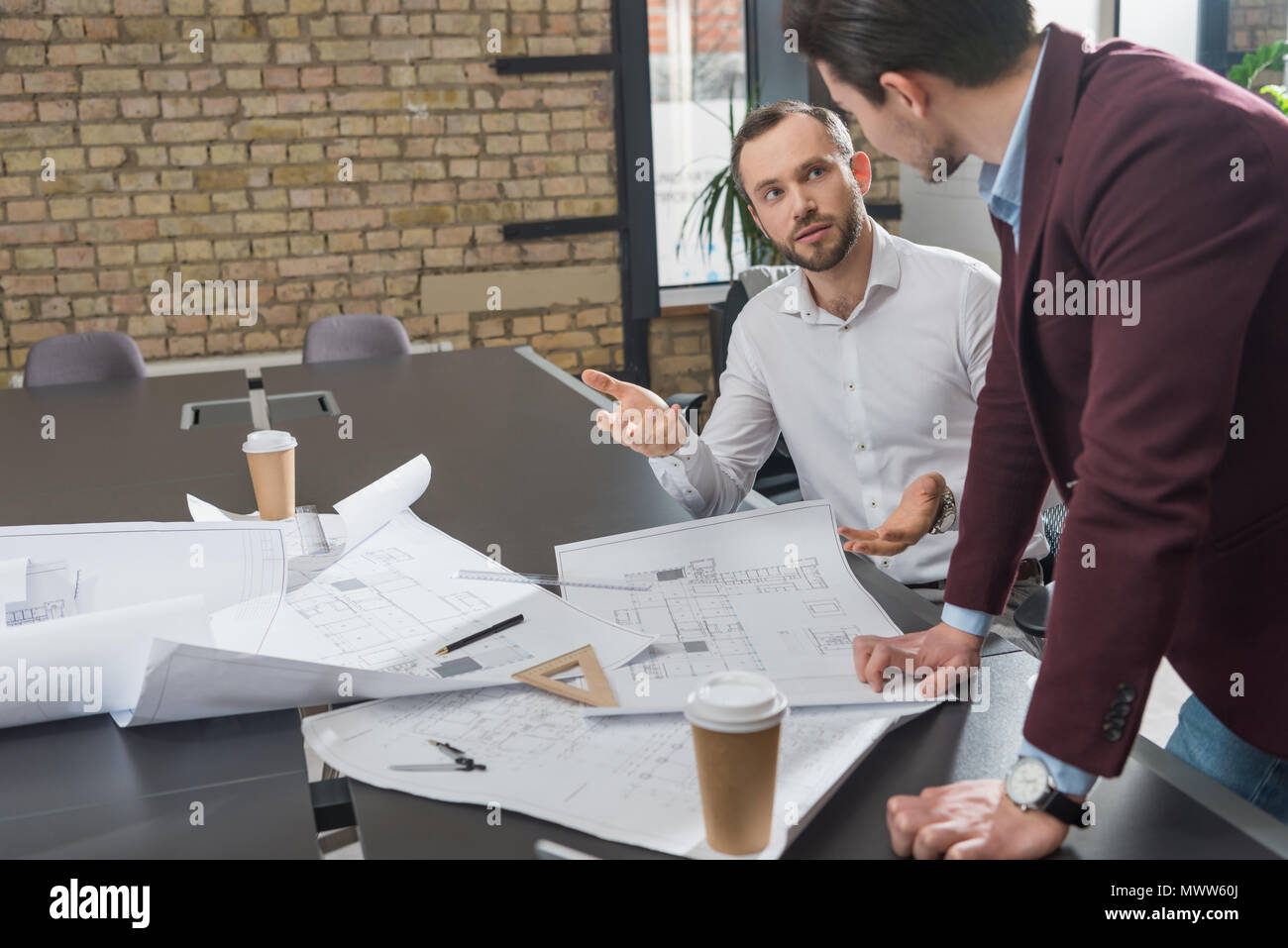 successful architects brainstorming over building plans at office Stock Photo