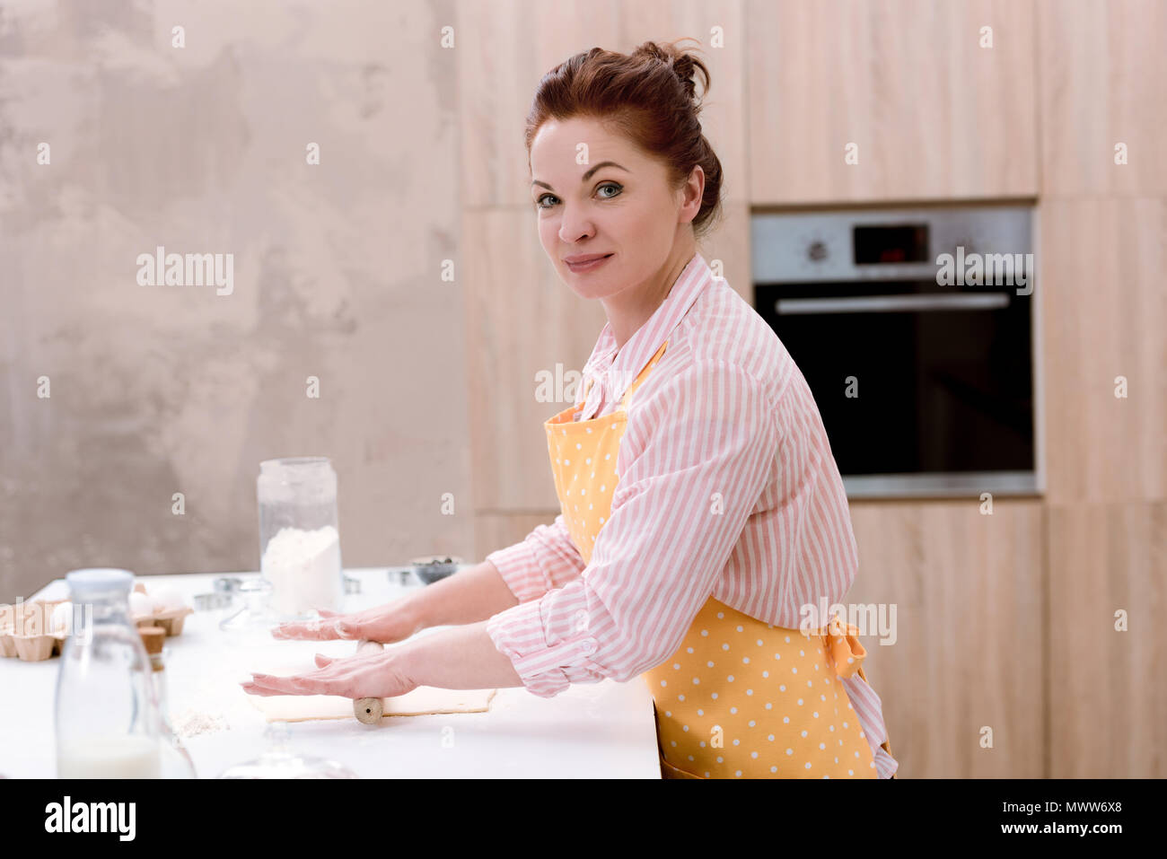 beautiful mature woman rolling dough for pastry at kitchen - Stock Image