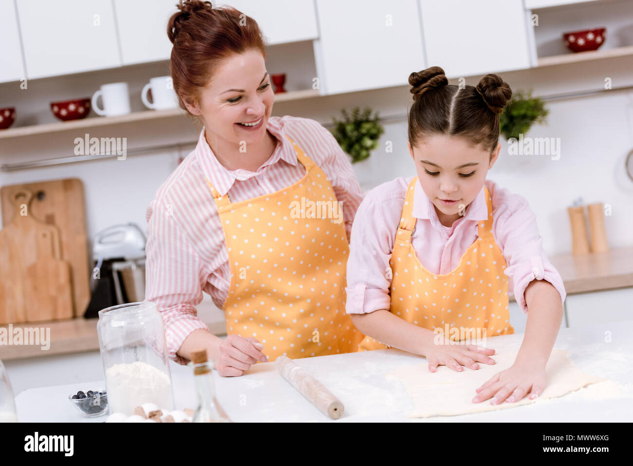 happy grandmother with little granddaughter rolling dough for cookies - Stock Image