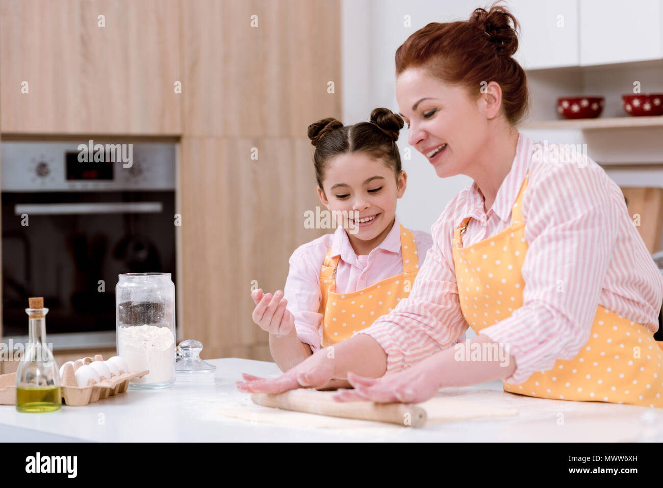 grandmother with little granddaughter rolling dough for cookies - Stock Image