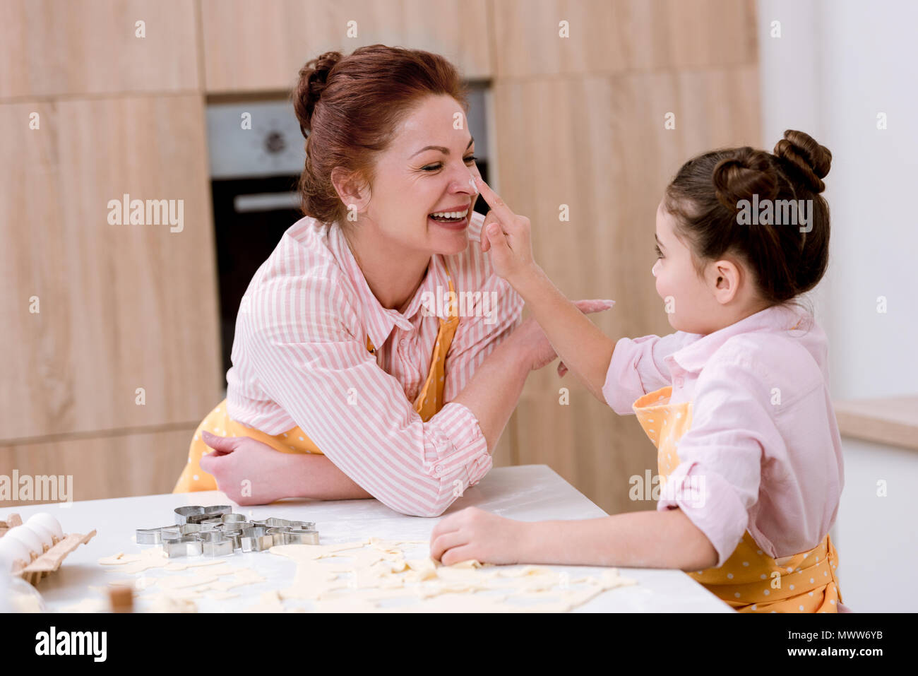 beautiful grandmother and little granddaughter playing with flour at kitchen while cooking - Stock Image
