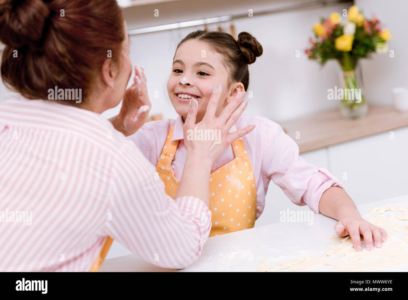 grandmother and little granddaughter playing with flour at kitchen while cooking - Stock Image