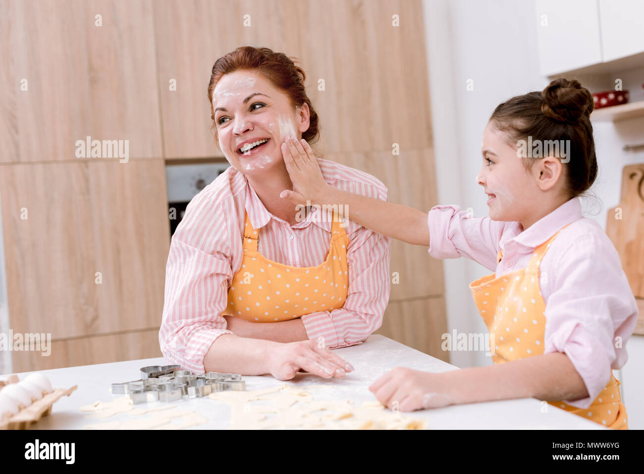 happy grandmother and little granddaughter playing with flour at kitchen while cooking - Stock Image
