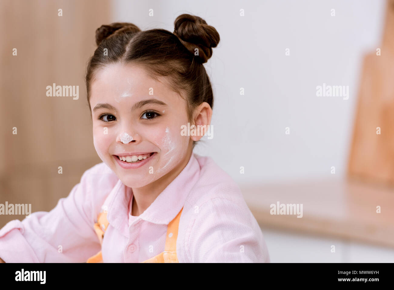 close-up portrait of little child with flour on face looking at camera - Stock Image