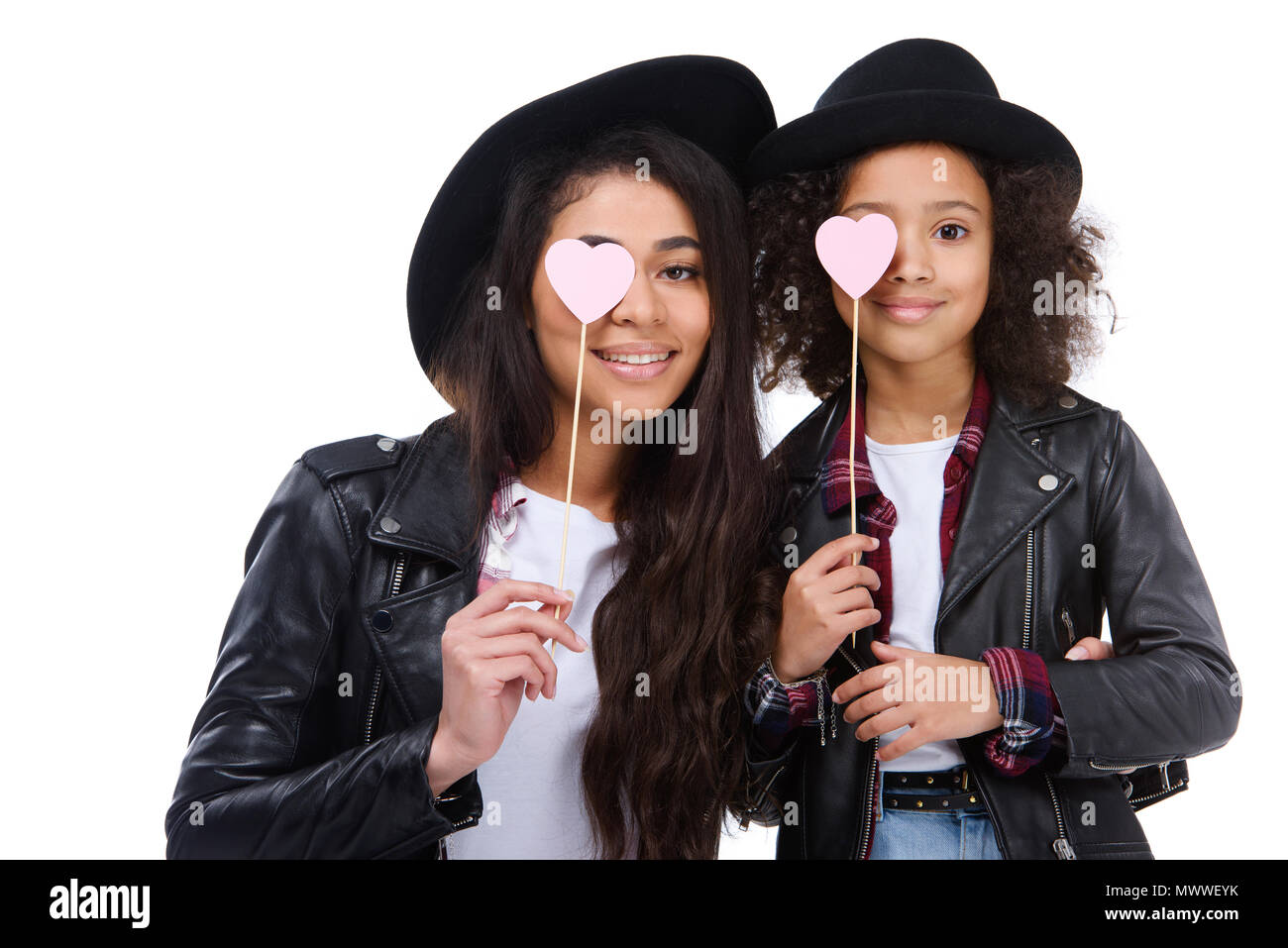 Mother And Daughter Covering Eyes With Heart Symbols On Sticks