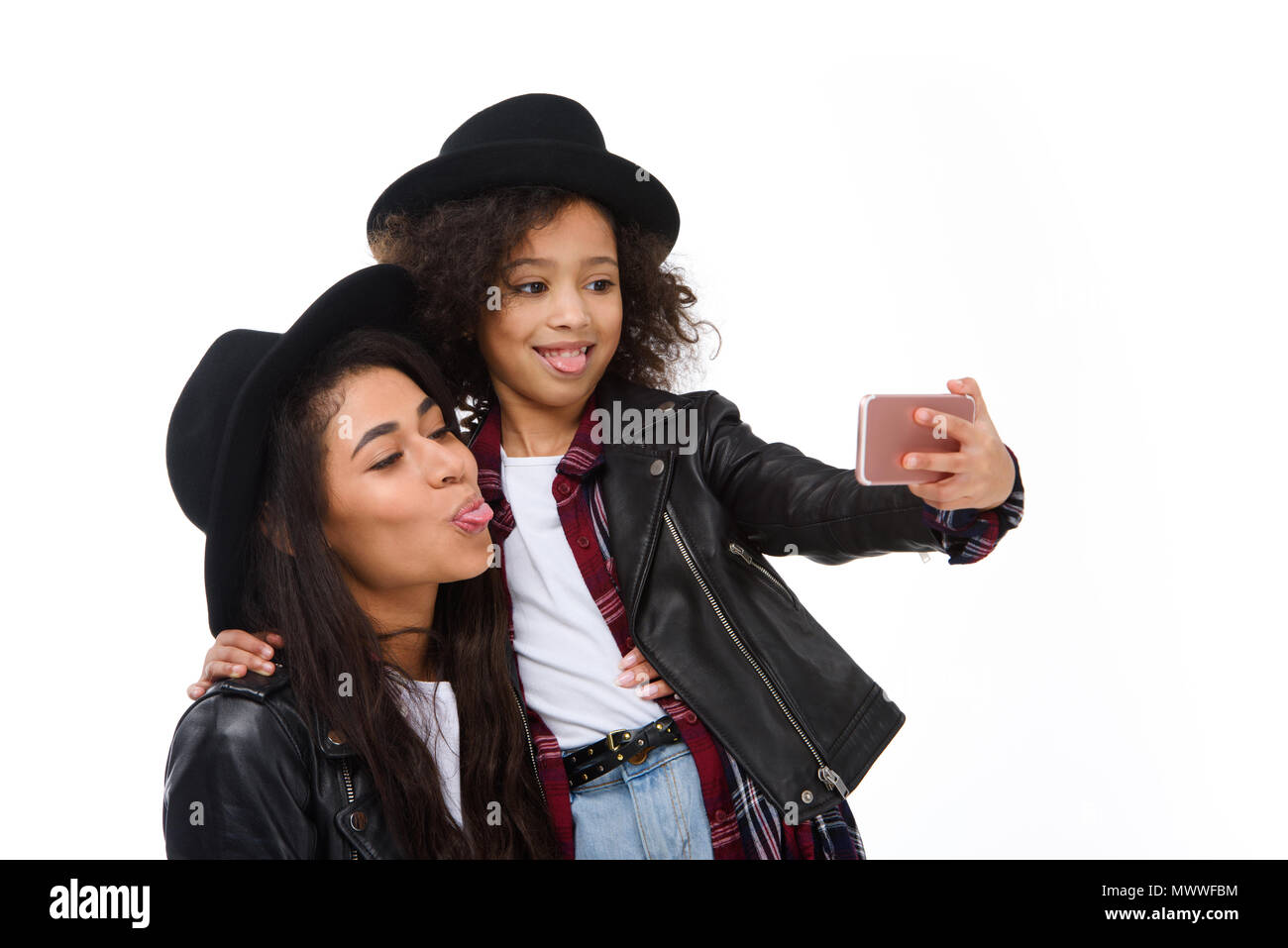 stylish mother and daughter taking selfie with smartphone and grimacing isolated on white - Stock Image