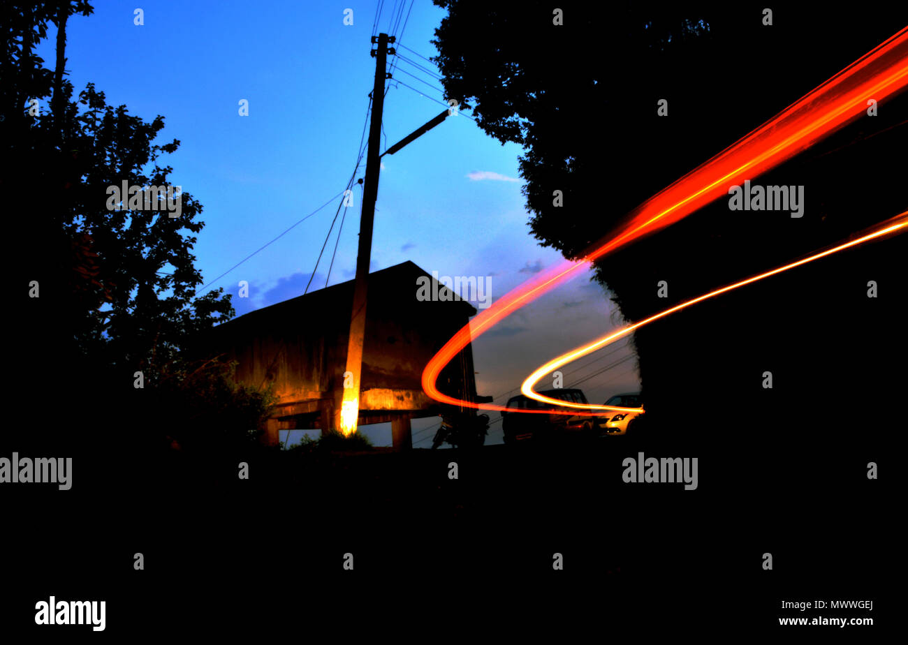 Light trails of a car in the mountains. - Stock Image