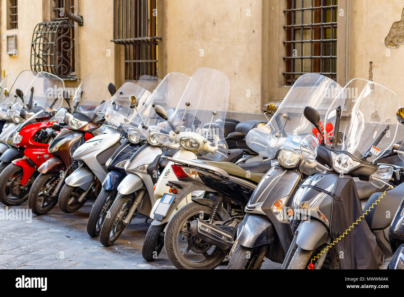 A typical street of Florence with motorcycle scooters parked in row in Italy - Stock Image