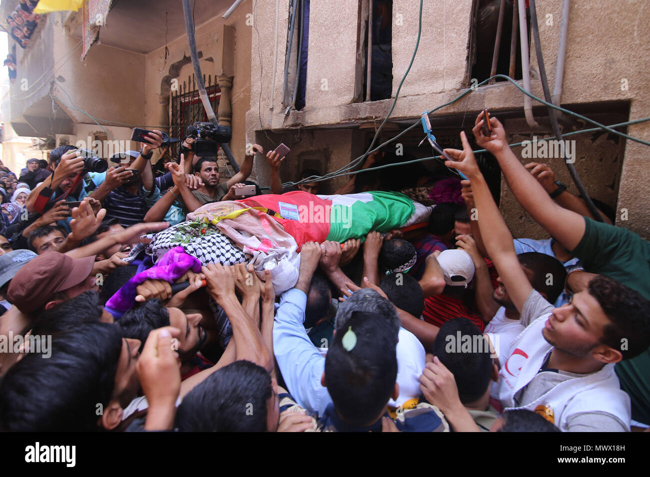 Gaza. 2nd June, 2018. Mourners carry the body of Razan al-Najjar during her funeral in the southern Gaza Strip City of Khan Yunis, on June 2, 2018. Thousands of outraged Palestinian mourners buried on Saturday the female paramedic who was shot dead by Israeli gunfire close to Gaza's border with Israel. Credit: Khaled Omar/Xinhua/Alamy Live News - Stock Image