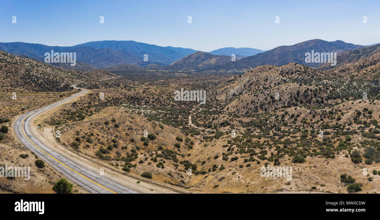 Panorama of vast desert wilderness and curving highway road through the emptiness. - Stock Image