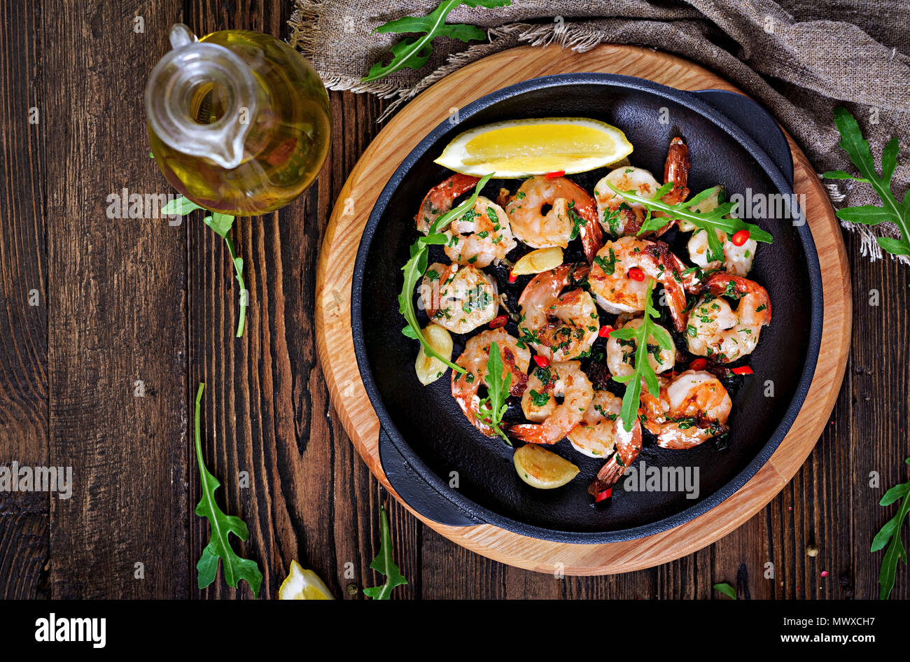 Prawns Shrimps roasted in garlic butter with lemon and parsley on wooden background. Healthy food. Top view. Flat lay. - Stock Image