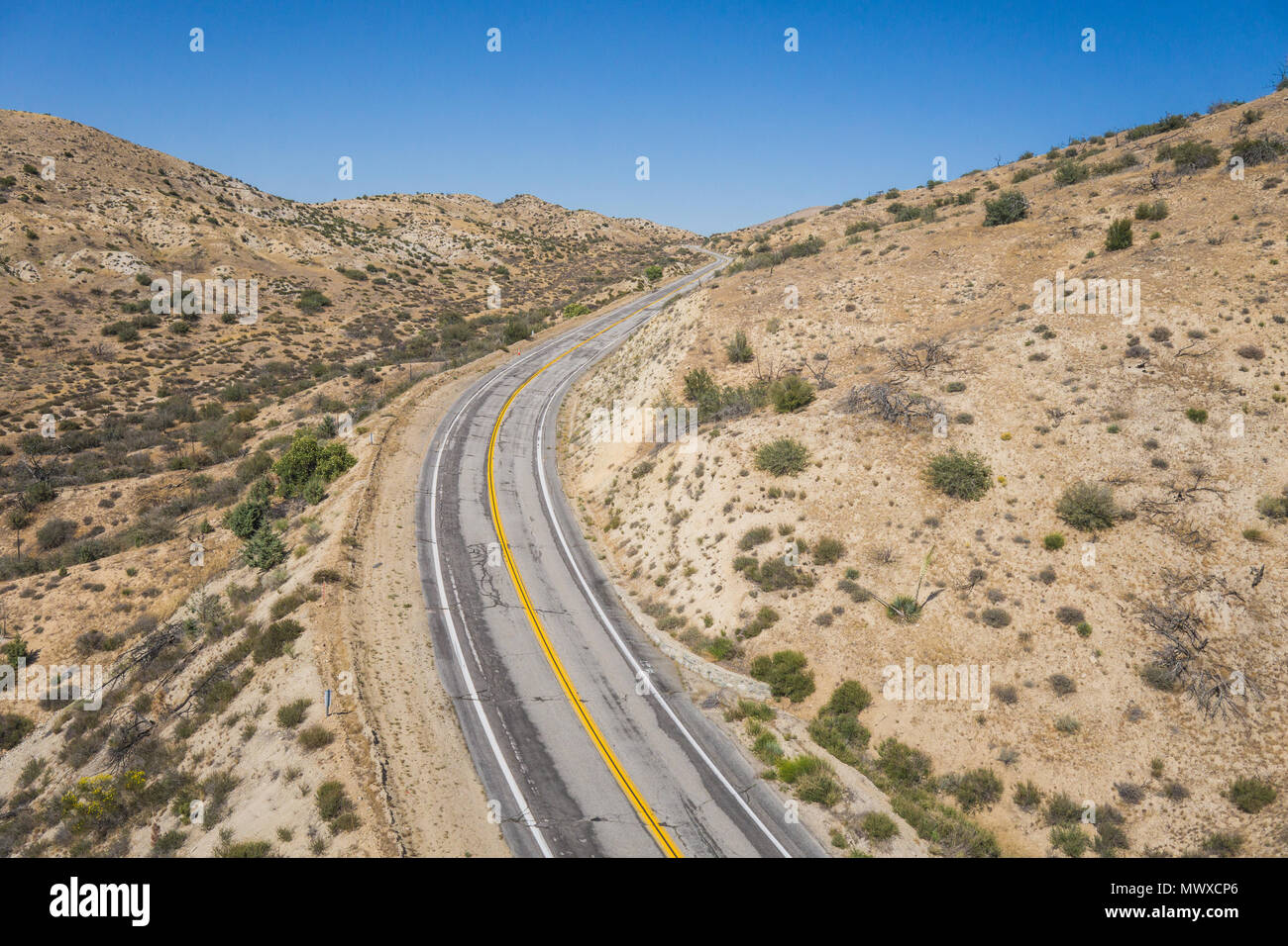 Asphalt highway bends around a curve in the empty wilderness of the American southwest. - Stock Image