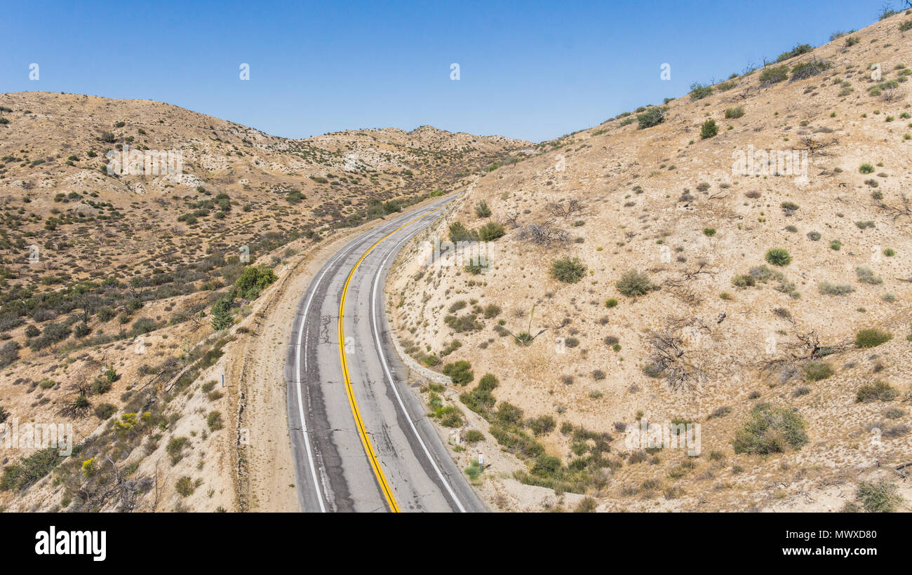 Bend in a desert road wrapping around a wilderness hillside. - Stock Image