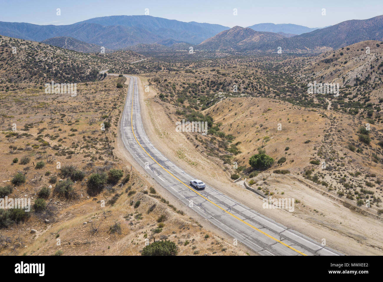 Single car on empty wilderness road in the Mojave Desert of southern California. - Stock Image