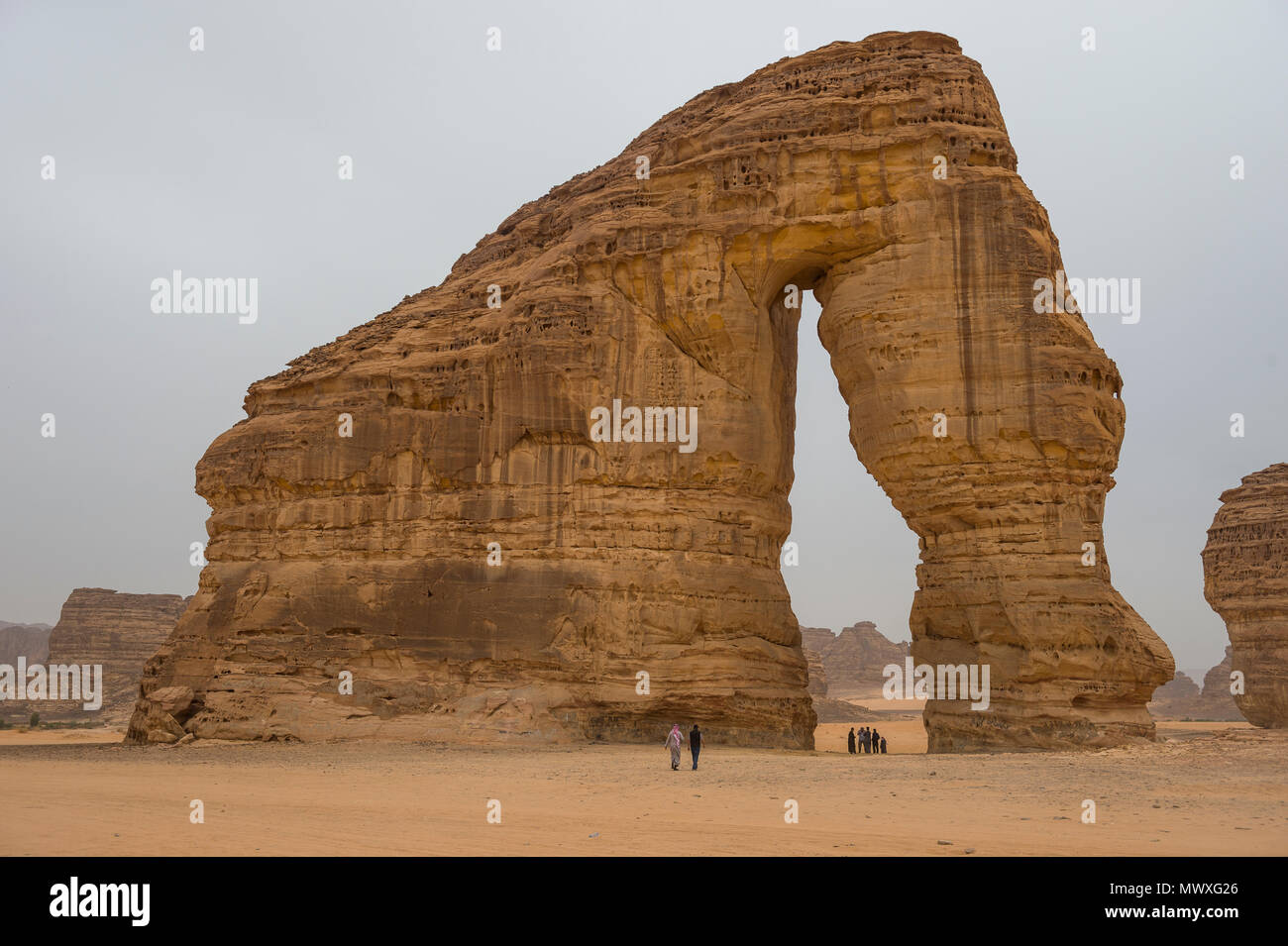 Locals standing in the giant arch of Elephant Rock, Al Ula, Saudi Arabia, Middle East - Stock Image
