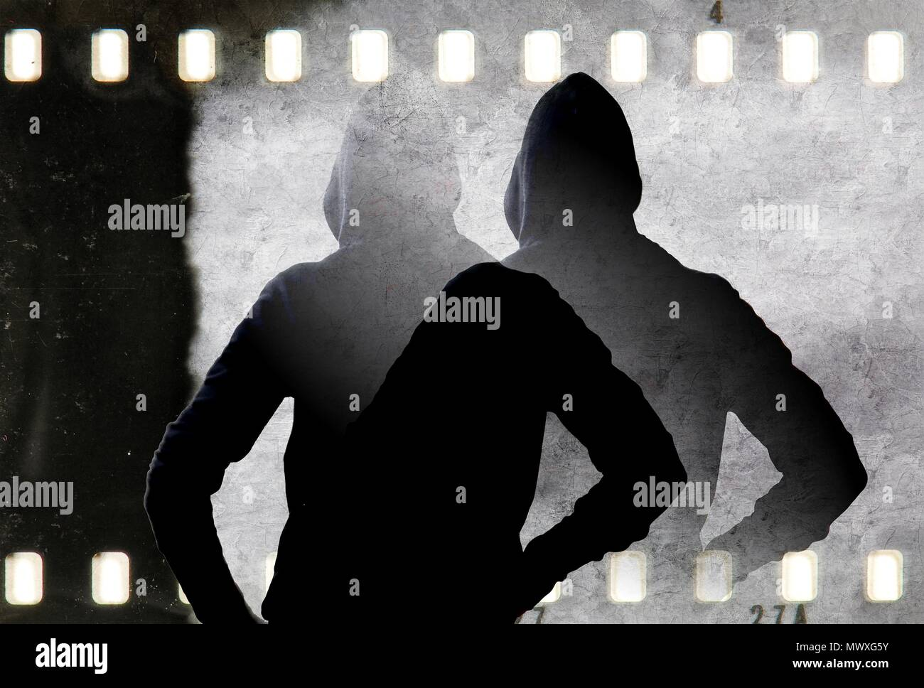 Vintage black and white doubled silhouette of young man with hooded sweatshirt and film strip frame. - Stock Image