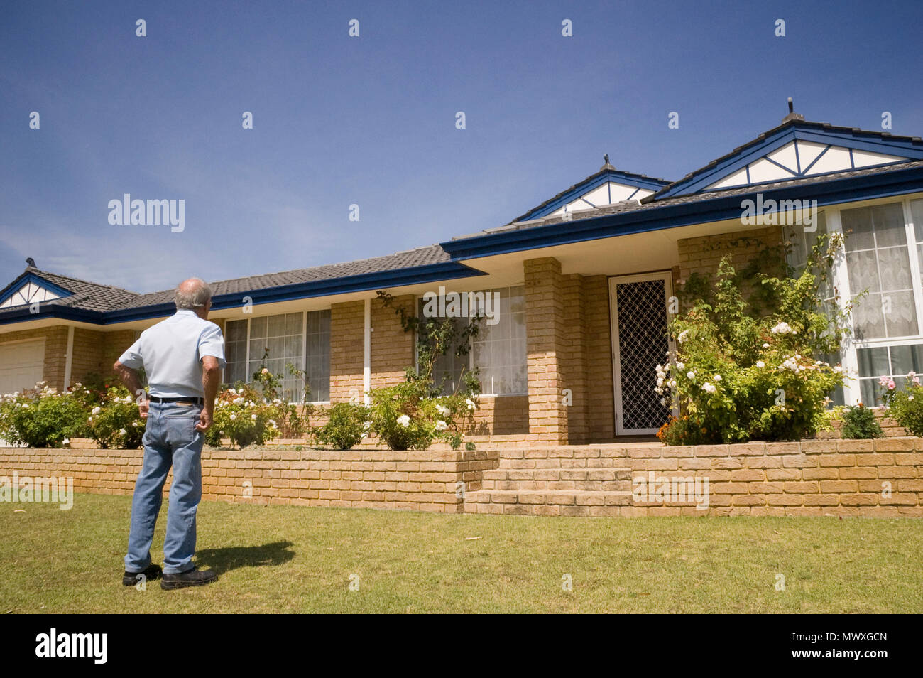 An elderly man standing in the front yard of his home, rear view. - Stock Image