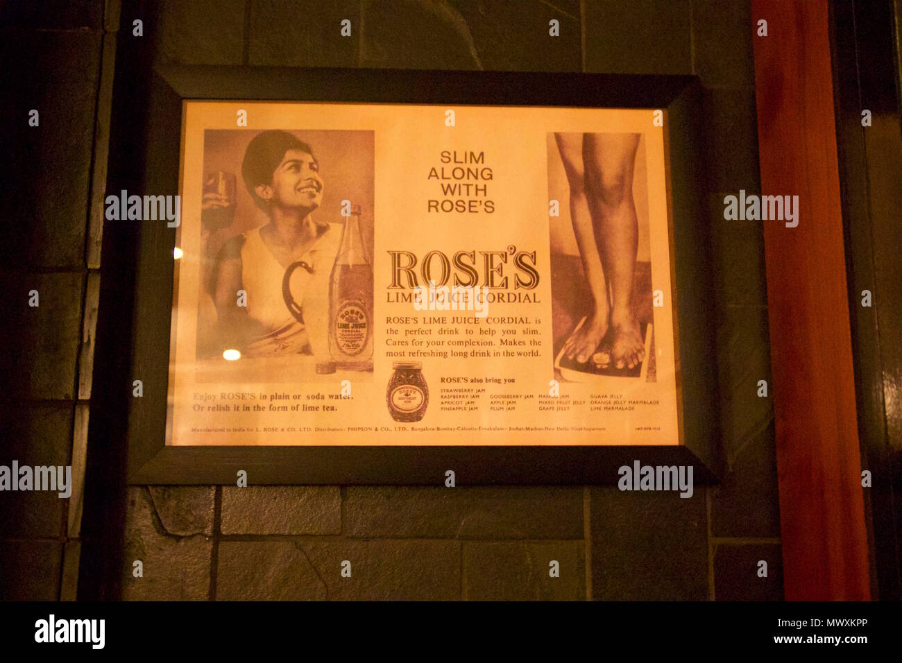 An old indian advert for Rose's Lime Juice Cordial in the bathrooms at Dishoom serving as decoration - Stock Image