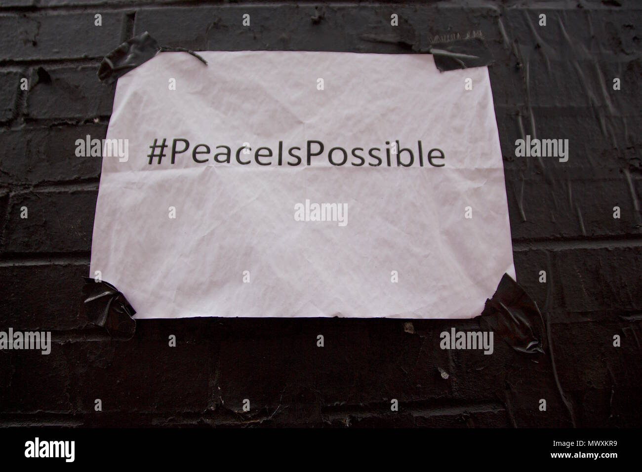 Taped white paper onto a wall on Ebor Street, Shoreditch, London saying #PeaceIsPossible, which is next to a peace wall mural by Ben EINE - Stock Image