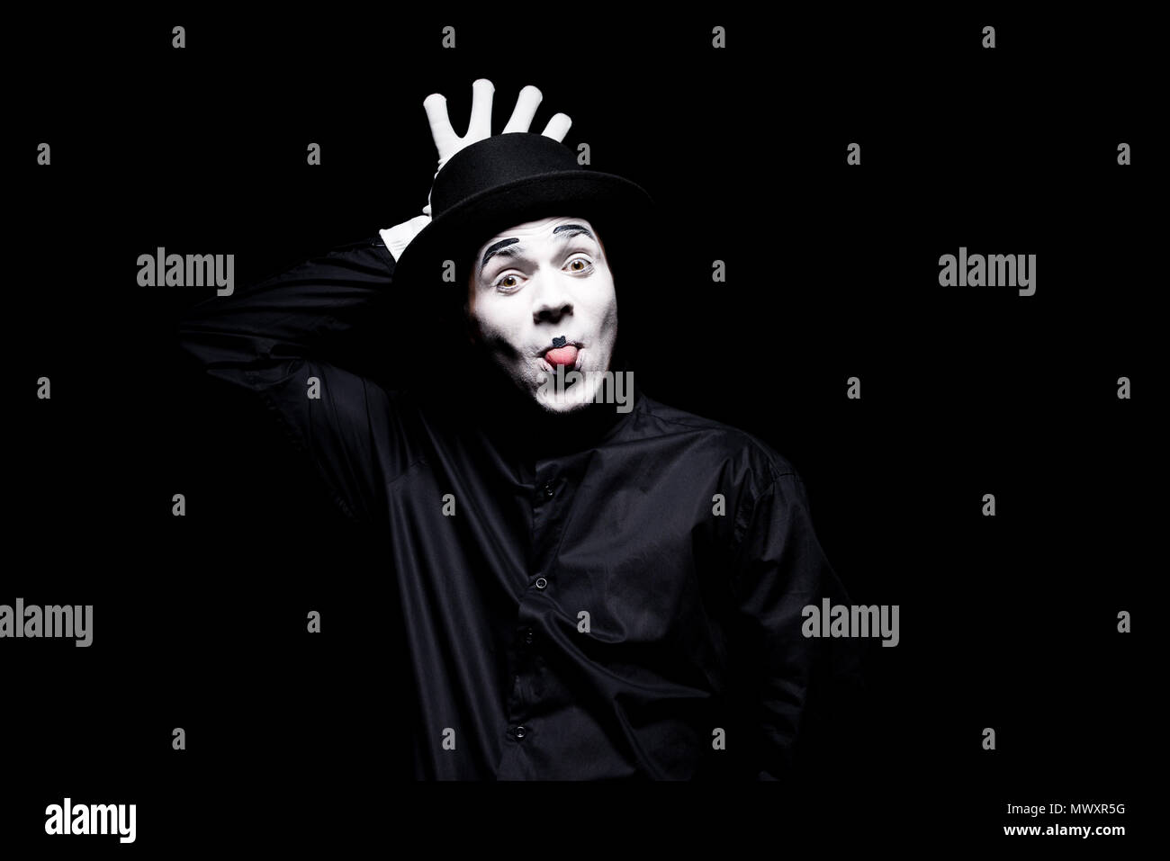 mime sticking tongue out and grimacing isolated on black - Stock Image