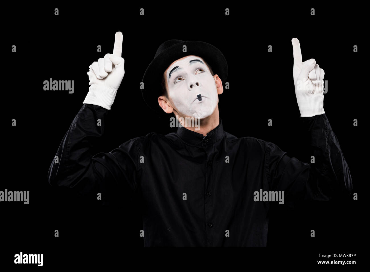 grimacing mime pointing on something isolated on black - Stock Image