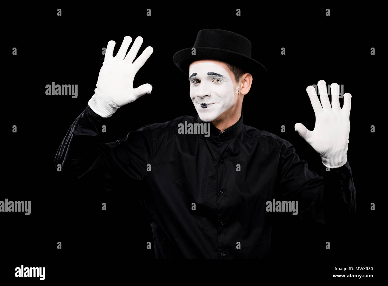 smiling mime performing and touching something isolated on black - Stock Image