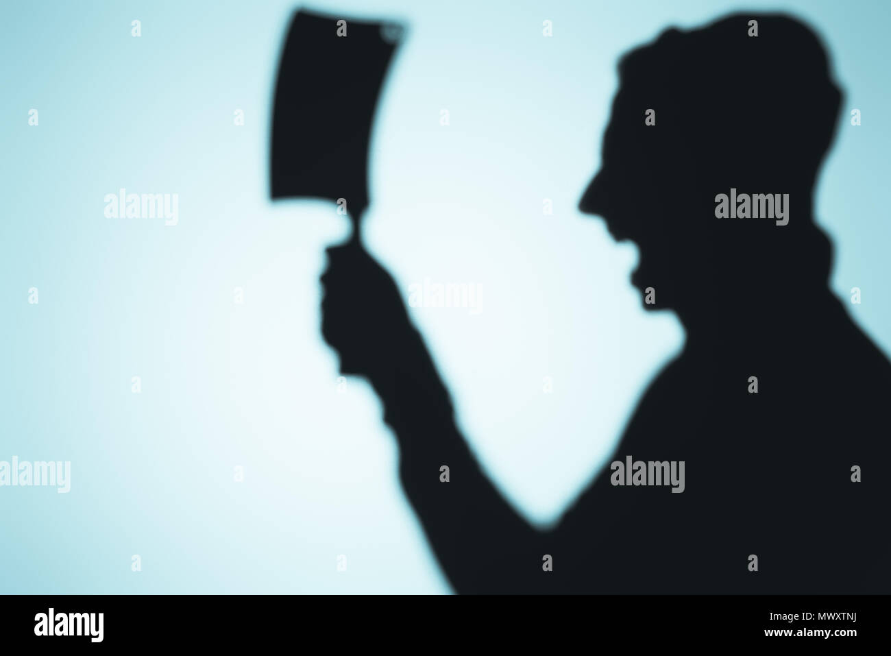 scary shadow of screaming person holding meat knife on blue Stock Photo