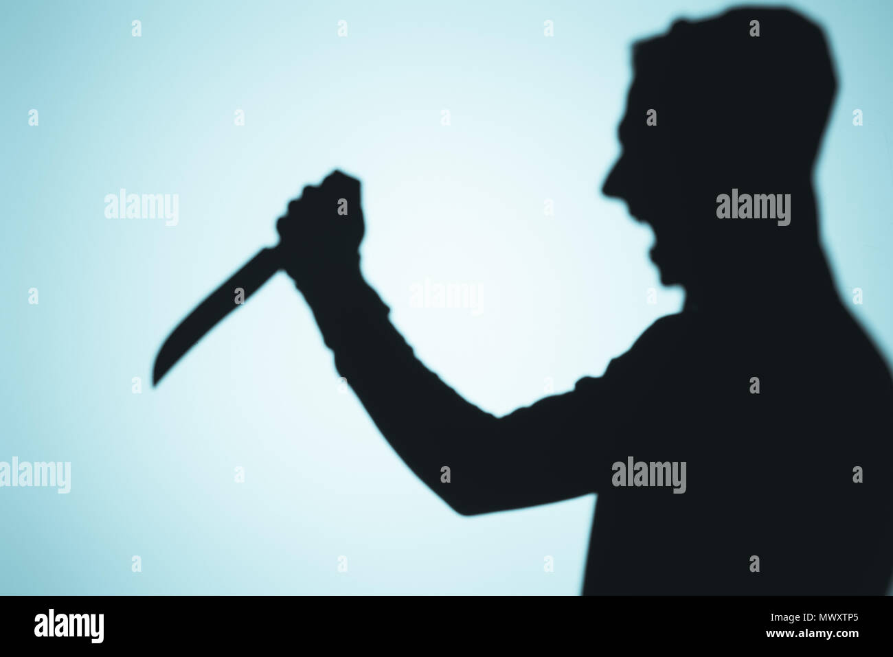 shadow of person screaming and holding knife on blue Stock Photo