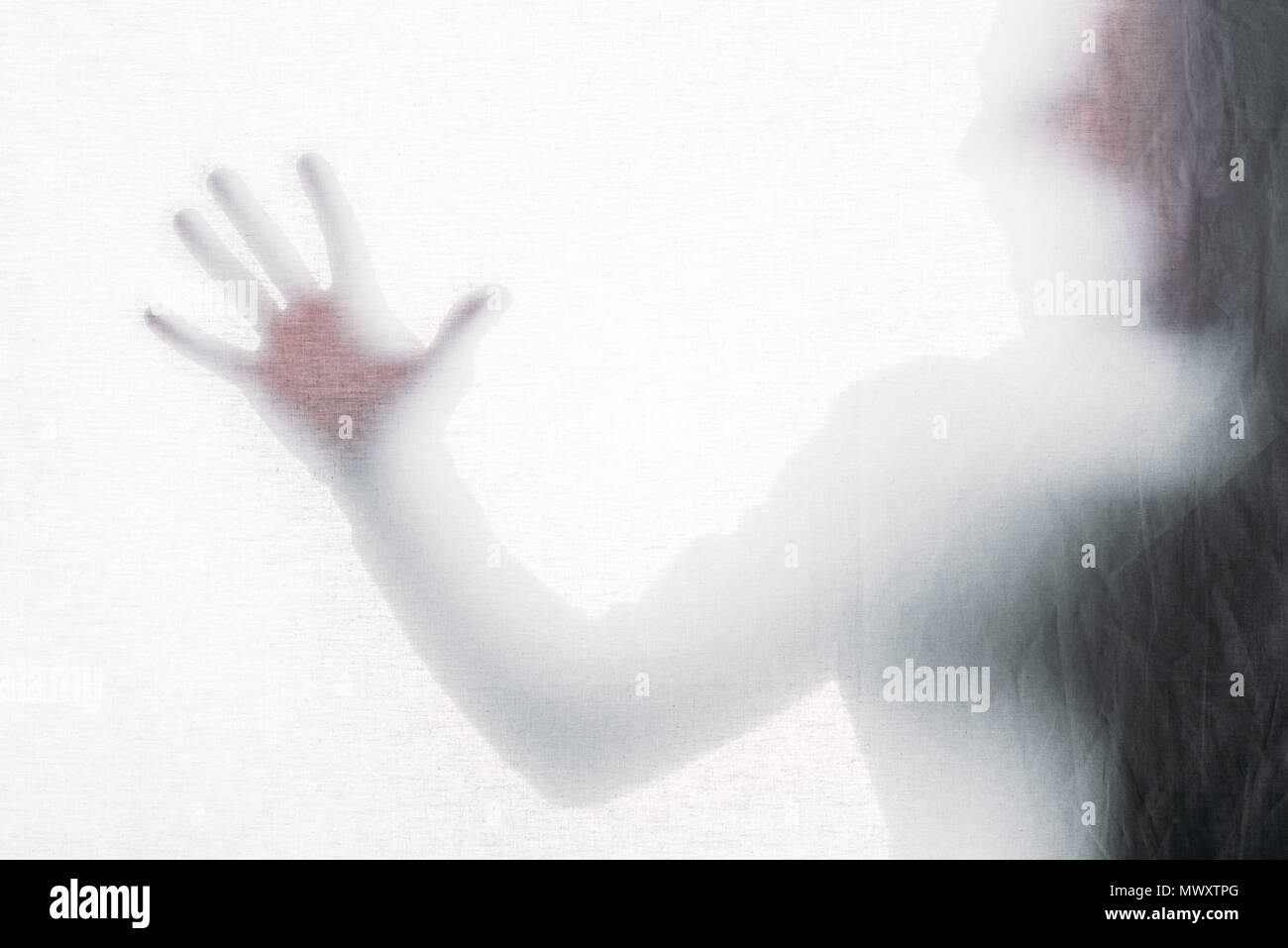 blurry silhouette of screaming person touching frosted glass Stock Photo