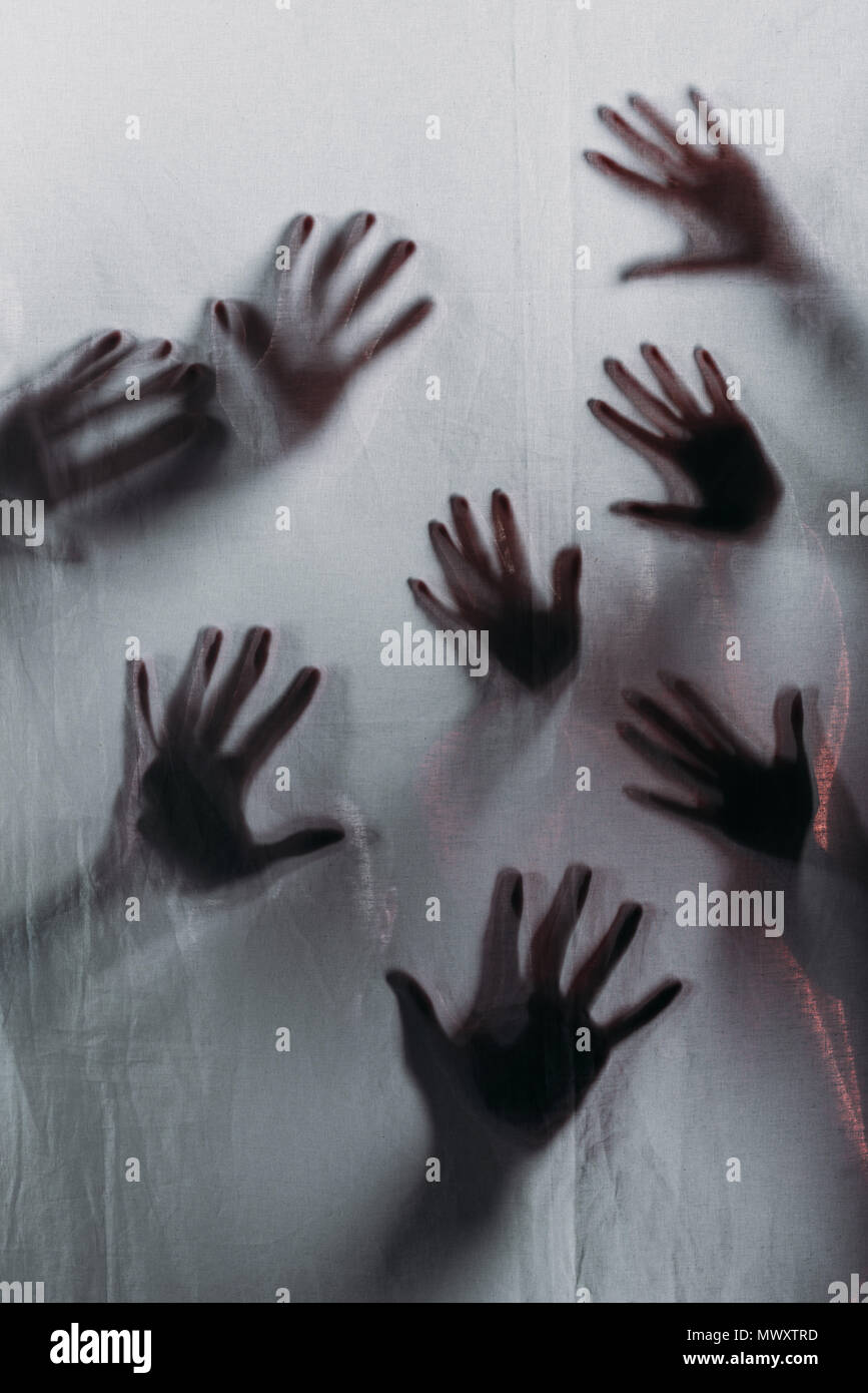 blurry scary silhouettes of human hands touching frosted glass - Stock Image