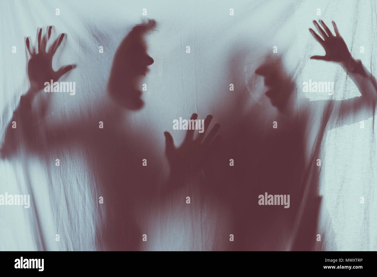 blurry scary silhouettes of screaming people - Stock Image
