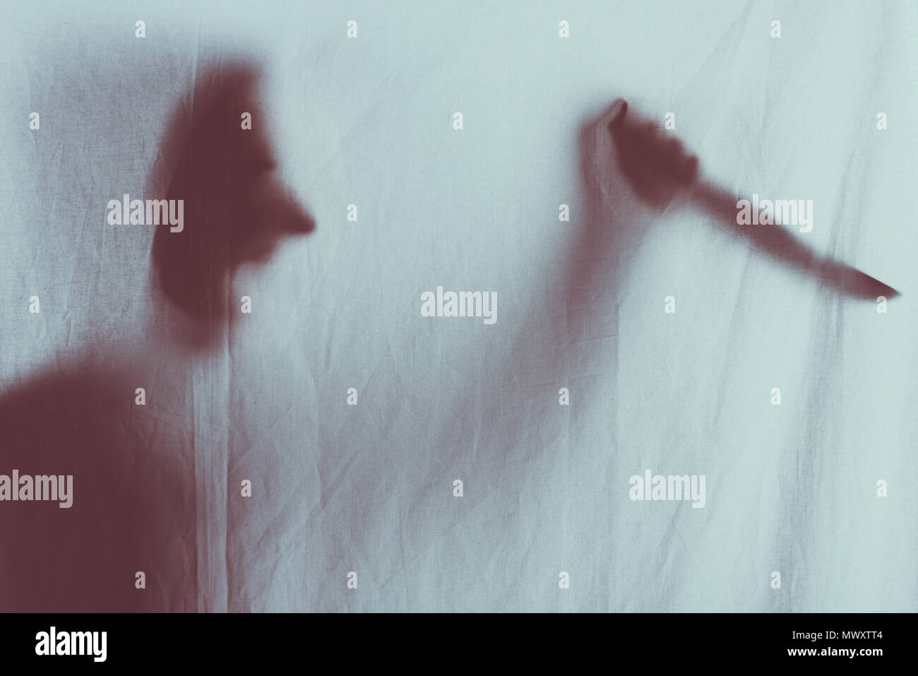 scary blurry silhouette of person screaming and holding knife behind veil Stock Photo