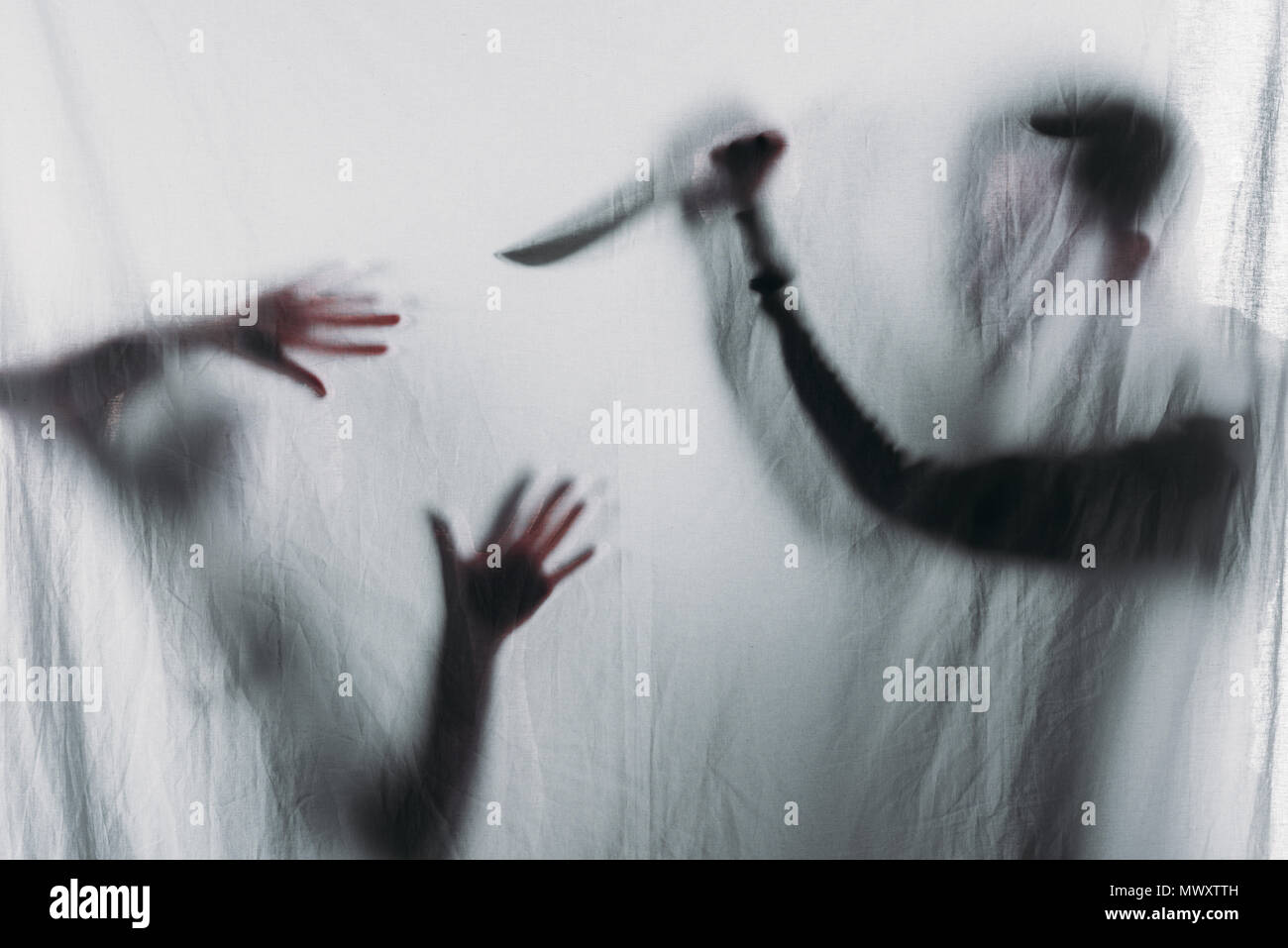 silhouette of someone holding knife and murdering victim, crime concept - Stock Image