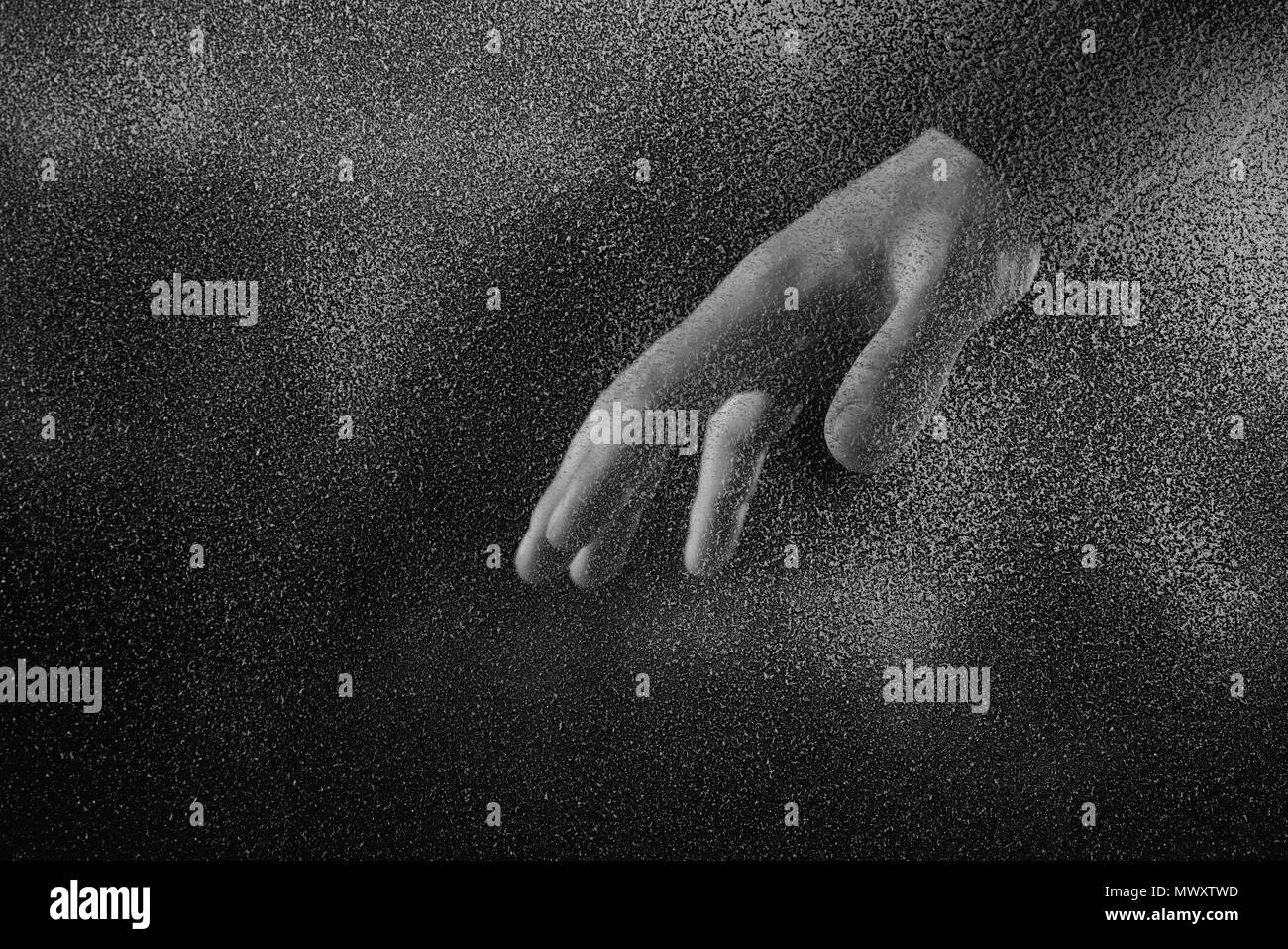cropped shot of person showing hand through frosted glass in darkness - Stock Image