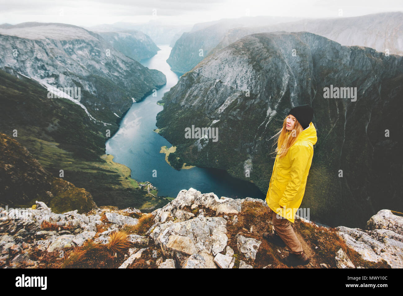 Woman traveler on mountain cliff standing alone traveling in Norway Lifestyle adventure vacations aerial fjord view girl wearing yellow raincoat walki - Stock Image