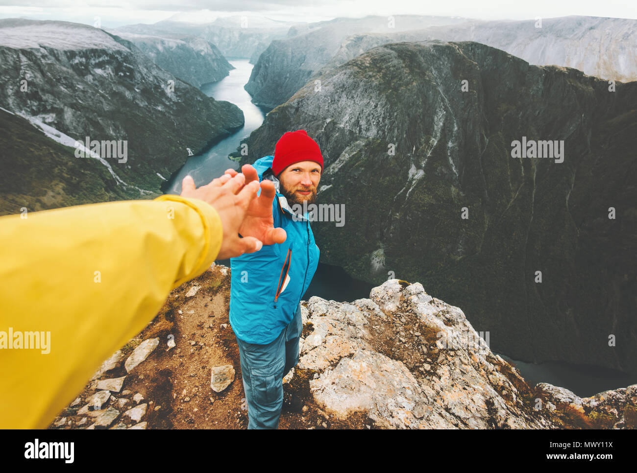 Couple adventurers in mountains follow helping hand traveling together lifestyle concept extreme vacations adventure weekend getaway in Norway - Stock Image