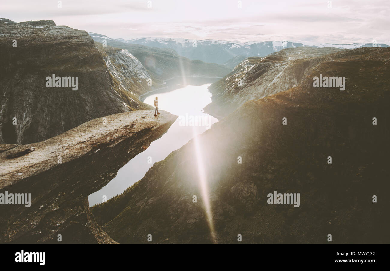 Traveler on Trolltunga cliff edge in Norway sunset mountains adventure travel lifestyle extreme vacations outdoor landscape famous landmarks - Stock Image