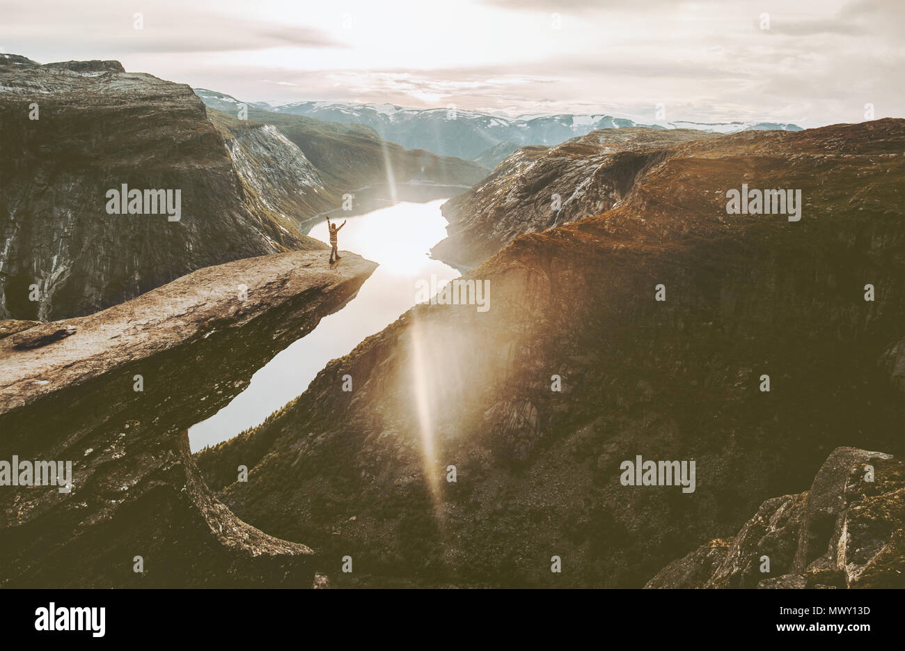 Tourist on Trolltunga cliff edge in Norway adventure travel lifestyle active vacations outdoor sunset mountains   landscape - Stock Image