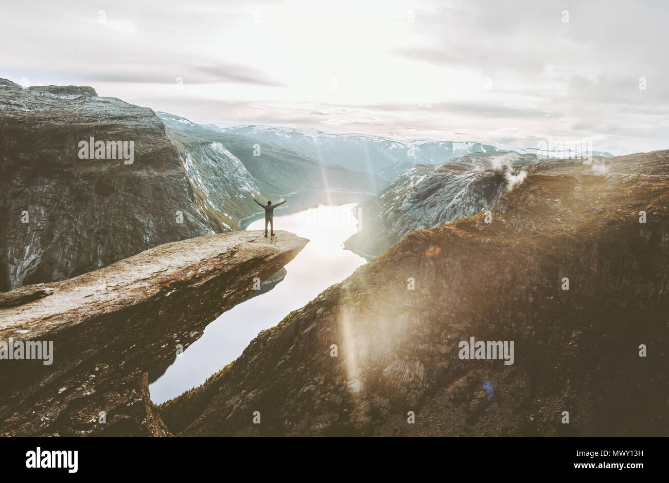 Man on Trolltunga cliff edge happy raised hands traveling in Norway adventure lifestyle extreme vacations outdoor sunset mountains landscape aerial vi - Stock Image