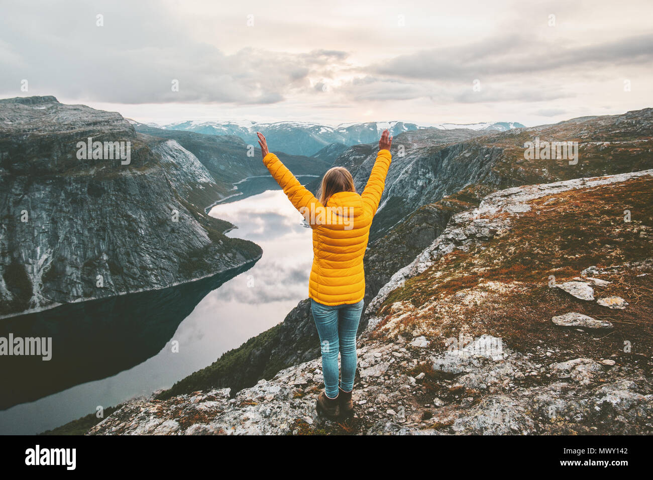 Happy woman raised hands on mountain summit traveling alone adventure lifestyle journey vacations aerial lake landscape success wellness emotions - Stock Image