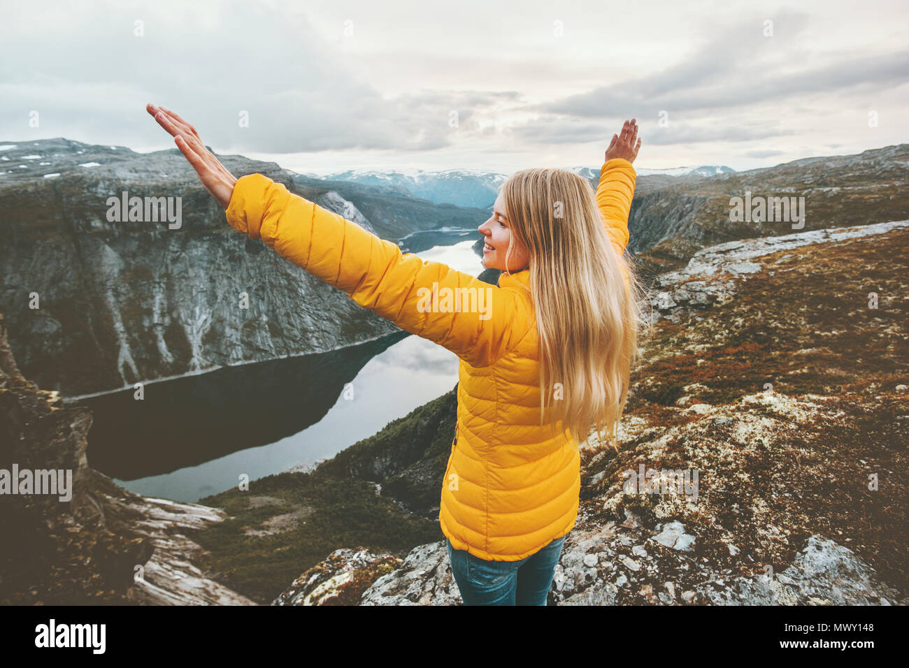 Young woman happy raised hands on mountain top travel adventure lifestyle journey vacations aerial lake landscape success wellness emotions - Stock Image