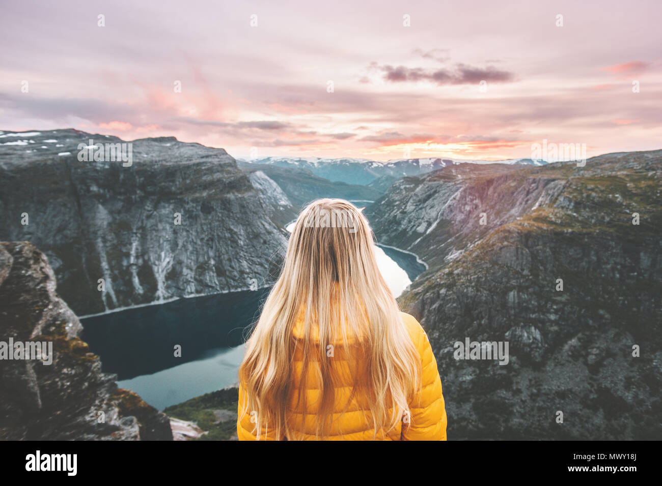 Woman traveling alone enjoying sunset mountains landscape adventure trip lifestyle vacations weekend getaway aerial Norway lake landscape - Stock Image