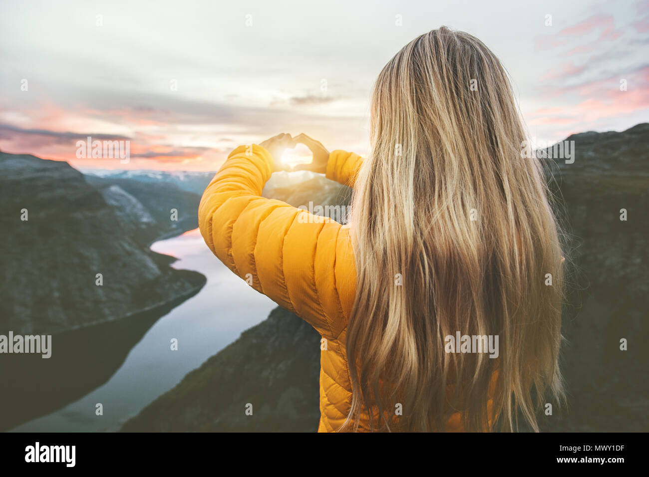 Woman traveling in sunset mountains hands heart symbol shaped Lifestyle emotional concept vacations weekend getaway aerial Norway landscape - Stock Image