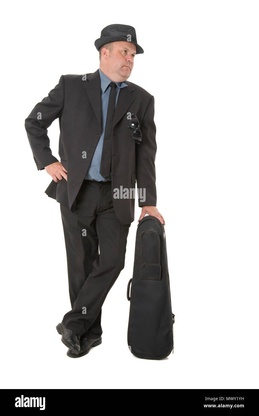 A guy in a suit leaning on an instrument case. - Stock Image