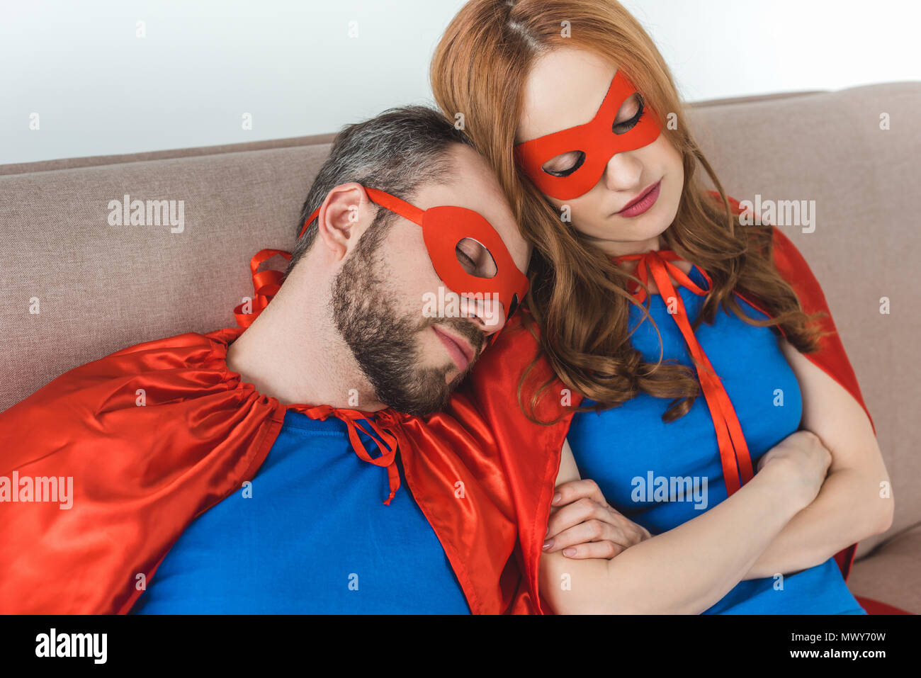 couple of superheroes in masks and cloaks sleeping together on couch