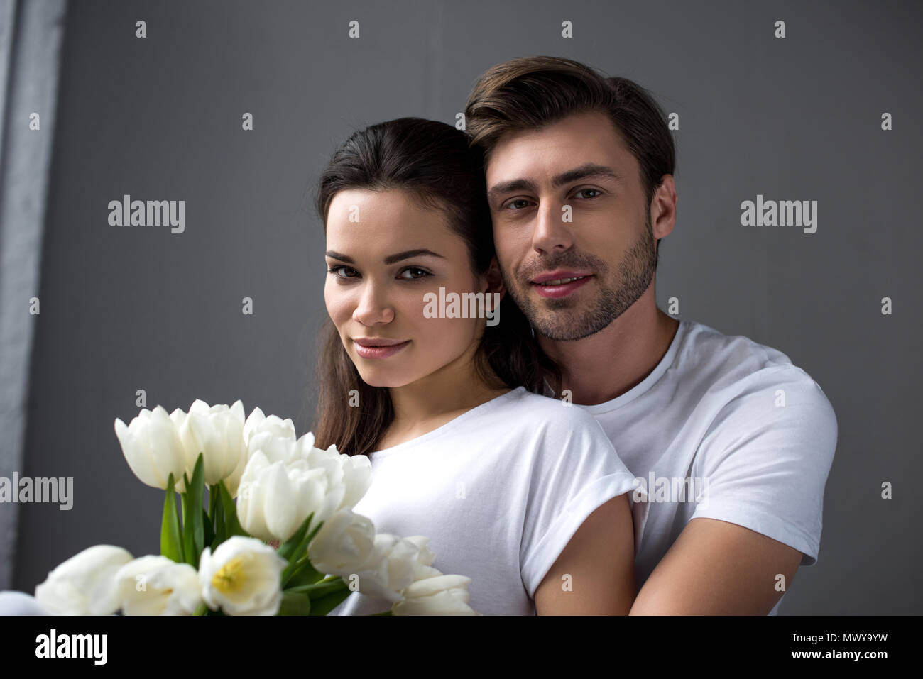 Smiling man and woman with flowers tenderly embracing in bedroom - Stock Image