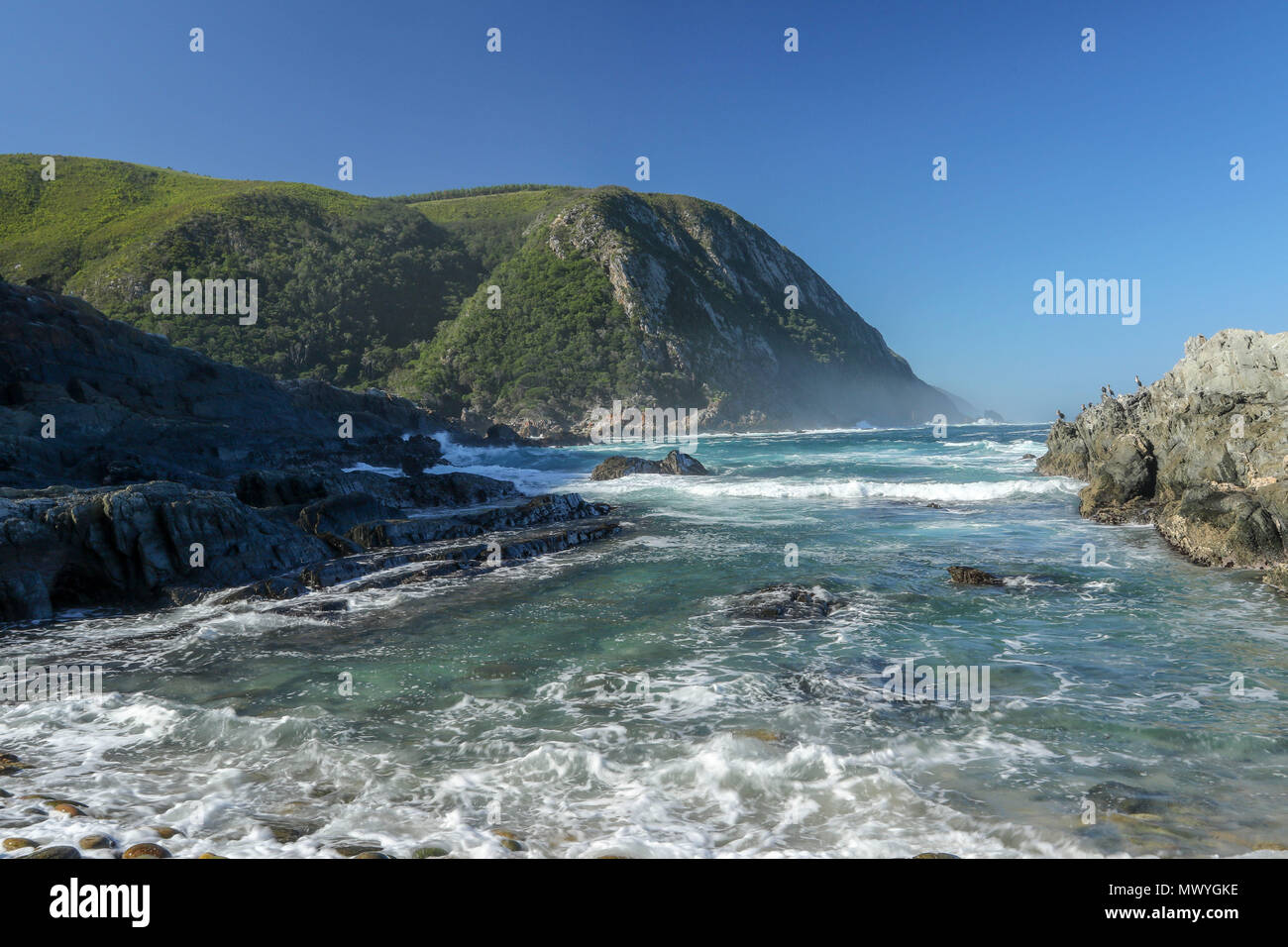 Incoming indian ocean tide with storms river mouth in the background from the Tsitsikamma National Park, garden route, Cape, south africa - Stock Image